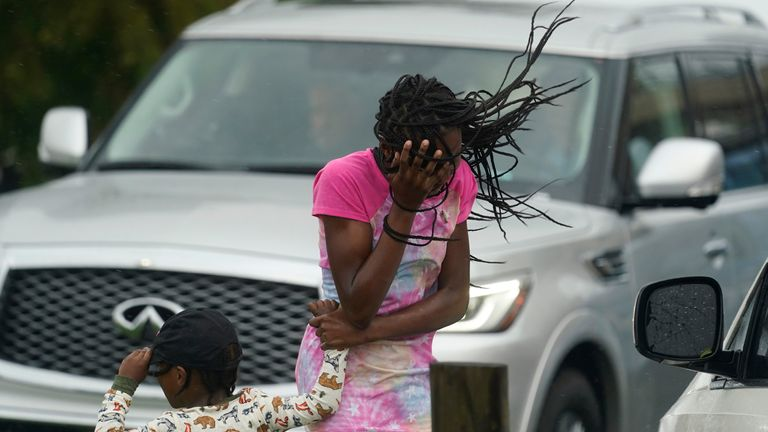A young girl blocks her face from the wind and rain produced by Hurricane Ida, Sunday, Aug. 29, 2021, in New Orleans, La. (AP Photo/Eric Gay)