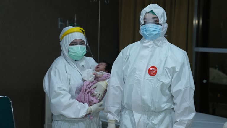 Dr Agus Susanto, a paediatrician at a hospital in Jakarta, and a nurse with a child
