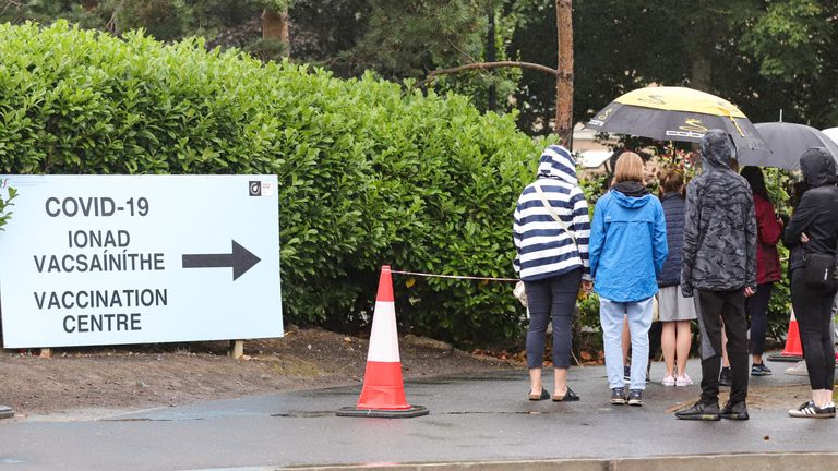 Parents and their children queue in the pouring rain outside the Citywest Covid-19 Vaccination Centre in Dublin as vaccinations of children and teenagers begins across Ireland, with more than 23 percent of those aged 12 to 15 registered to receive the jab. Picture date: Saturday August 14, 2021.
