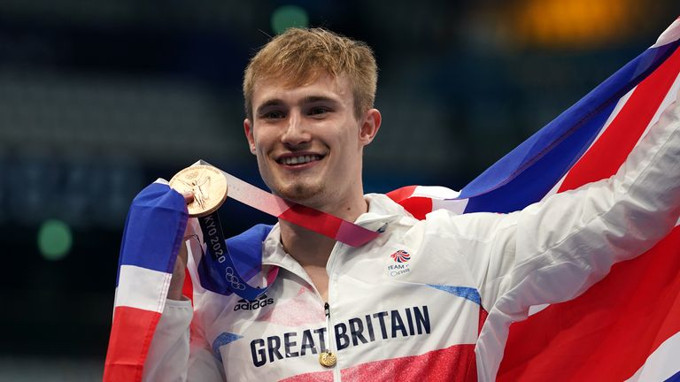 Laugher celebrates on the podium with his bronze medal