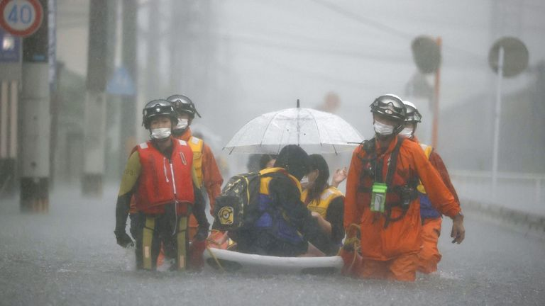 Firefighters transport stranded residents through a road flooded by heavy rain in Kurume, Fukuoka prefecture. Pic: Kyoto/via Reuters