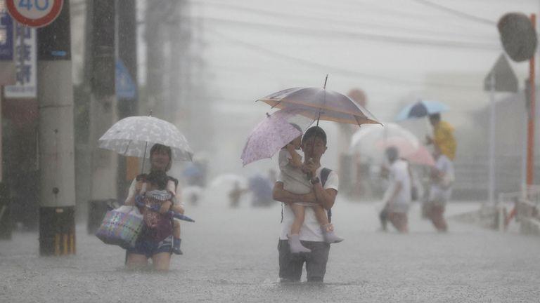 People walk through a flooded road in Kurume, Fukuoka prefecture. Pic: Kyodo/via Reuters