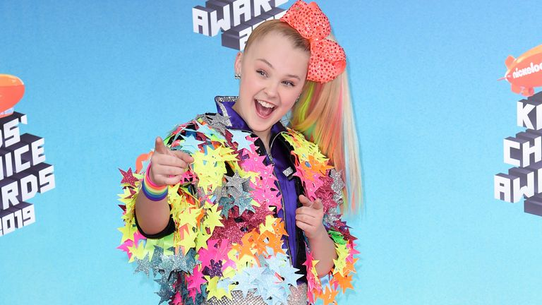 """FILE - JoJo Siwa arrives at the Nickelodeon Kids' Choice Awards on March 23, 2019, In Los Angeles. Siwa will compete as part of the first same-sex pairing on """"Dancing With the Stars"""" for the show's upcoming 30th season. (Photo by Richard Shotwell/Invision/AP, File)"""