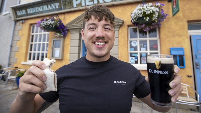 Jordan Leckey holding a celebrity jam sandwich and pint of Guinness outside Pier 36 in Donaghadee after setting a new world record time for swimming from Northern Ireland to Scotland. Picture date: Tuesday August 3, 2021.