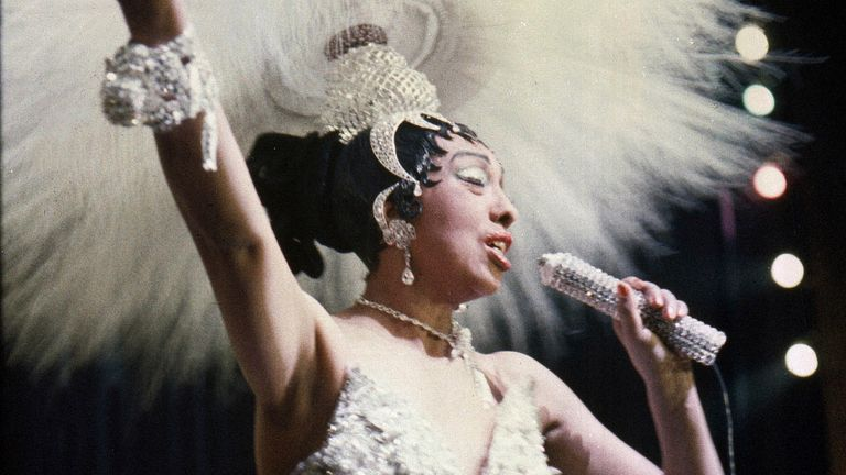 """Entertainer Josephine Baker holds a rhinestone-studded microphone as she performs during her show """"Paris, mes Amours"""" at the Olympia Music Hall in Paris, France. Pic: AP"""