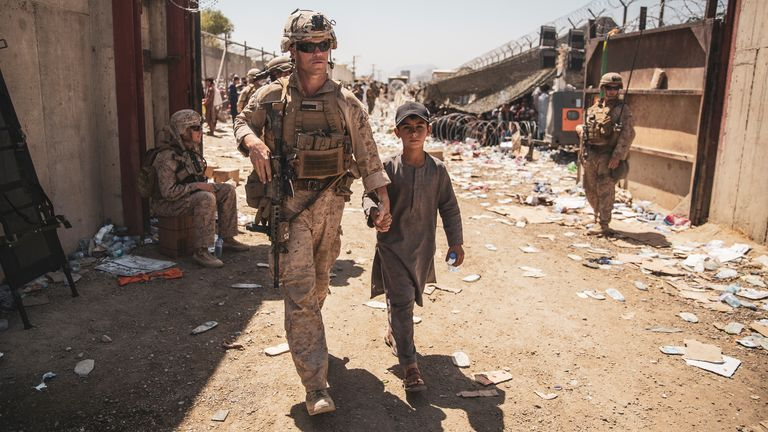 A U.S. Marine escorts a child to his family during an evacuation at Hamid Karzai International Airport in Kabul, Afghanistan. Pic: Sgt. Samuel Ruiz/U.S. Marine Corps/Reuters