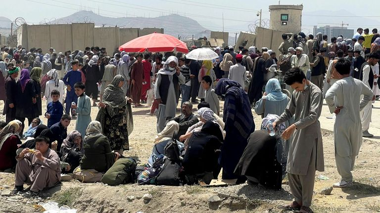 People wait outside Hamid Karzai International Airport in Kabul, Afghanistan August 17, 2021. REUTERS/Stringer