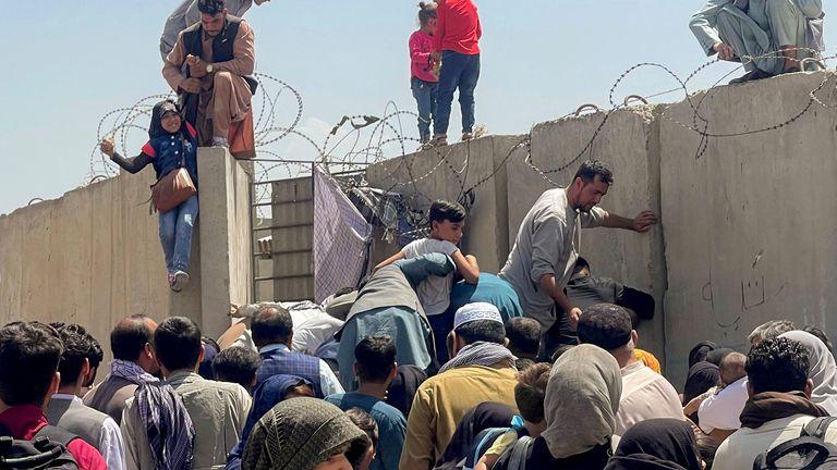 A man pulls a girl to get inside Hamid Karzai International Airport in Kabul
