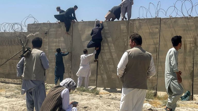 People attempt to leap a wall into Kabul airport