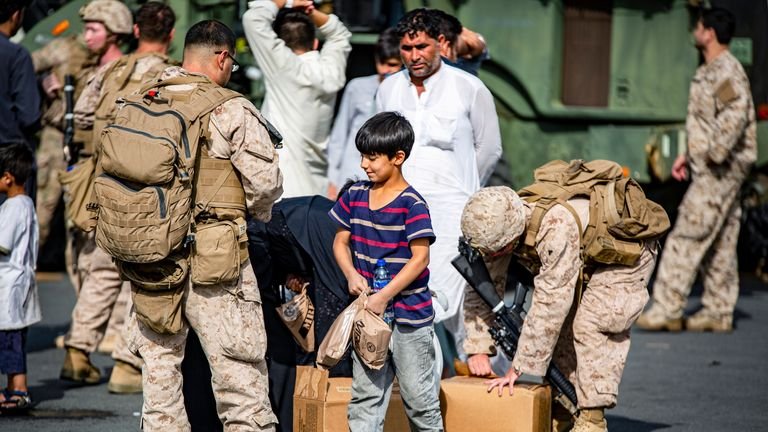 US marines pass out food to evacuees at Hamid Karzai International Airport. Pic: AP