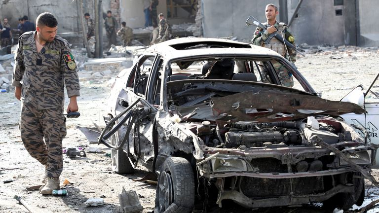 A member of Afghan security forces looks at a damaged car at the site of yesterday's night-time car bomb blast in Kabul. Pic: Reuters