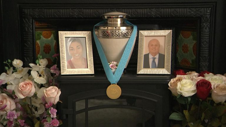 The Olympian's gold medal sits between a framed picture of herself and her late grandfather