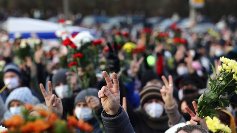 People flash the victory sign as they gather outside a church during a memorial service for Roman Bondarenko, an anti-government protester who died in hospital following what witnesses said was a severe beating by security forces, in Minsk, Belarus November 20, 2020. BelaPAN via REUTERS ATTENTION EDITORS - THIS IMAGE WAS PROVIDED BY A THIRD PARTY. MANDATORY CREDIT.