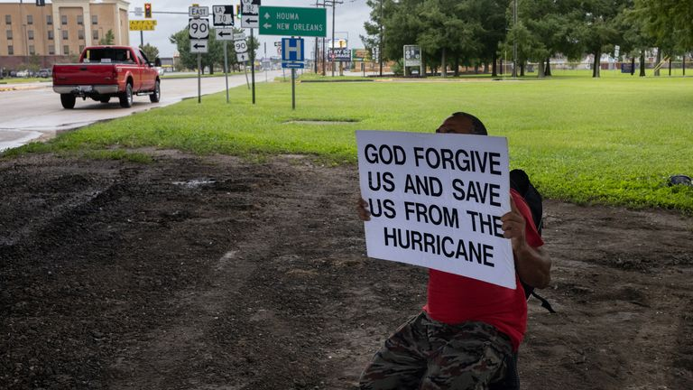A man holds a placard hours before the arrival of Hurricane Ida, in Morgan City, Louisiana (Pic: AP)