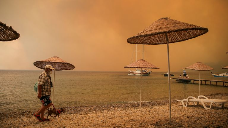 A man walks with his dog on the beach of smoke-engulfed Mazi area as wildfires rolled down the hill toward the seashore, in Bodrum, Mugla, Turkey. Pic: AP