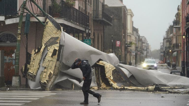 A man passes by a section of roof that was blown off of a building in the French Quarter in New Orleans (Pic: AP)