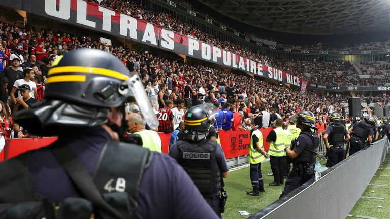A heavy police presence keeps watch on the Nice fans following the pitch invasion
