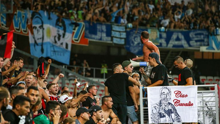 Nice fans cheer on their side as the travelling Marseille fans are pictured in the background