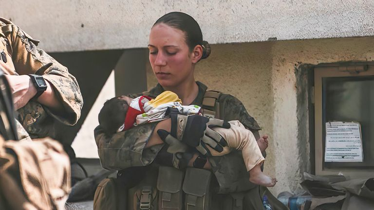 Nicole Gee calms an infant during an evacuation at Hamid Karzai International Airport in Kabul. Pic: AP