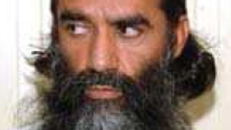Norullah Nori in the white suit of an obedient Guantanamo detainee
