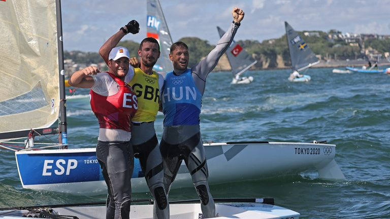 Team GB's Giles Scott celebrates his Finn class gold medal with Joan Cardona of Spain and Hungary's Zsombor Berecz, who pushed Scott all the way
