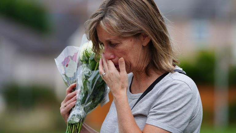 A woman holds back tears as she lays flowers in memory of the victims