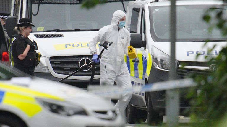 A police investigator carries a tripod and evidence markers in Royal Navy Avenue in the Keyham area of Plymouth