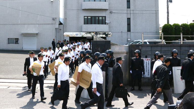 Police leave the building of Kudo-kai following a raid in 2014