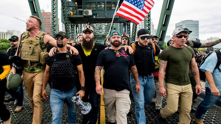 organizer Joe Biggs, in green hat, and Proud Boys Chairman Enrique Tarrio, holding megaphone, march with members of the Proud Boys and other right-wing demonstrators march across the Hawthorne Bridge during a rally in Portland