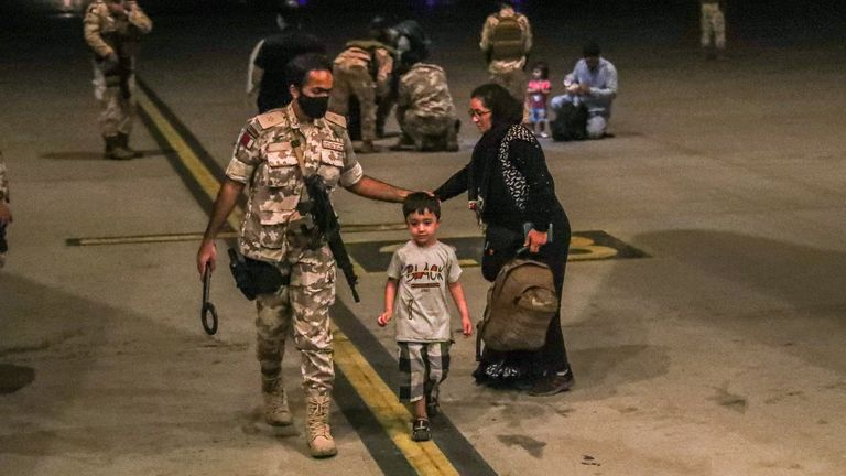 A member of the Qatar Air force walks next to a boy evacuated from Afghanistan, at Al-Udeid airbase in Doha, Qatar in this recent undated handout. Government Communications Office of the State of Qatar/Handout via REUTERS ATTENTION EDITORS - THIS PICTURE WAS PROVIDED BY A THIRD PARTY. NO RESALES. NO ARCHIVES.
