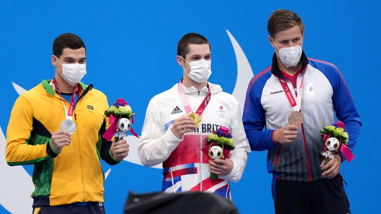 Great Britain's Reece Dunn (centre) poses with his gold medal on the podium after winning the S14 200m freestyle