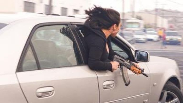 The woman was holding the automatic rifle while leaning out of the Cadillac's window. Pic: San Francisco Police/@SFTrafficSafety