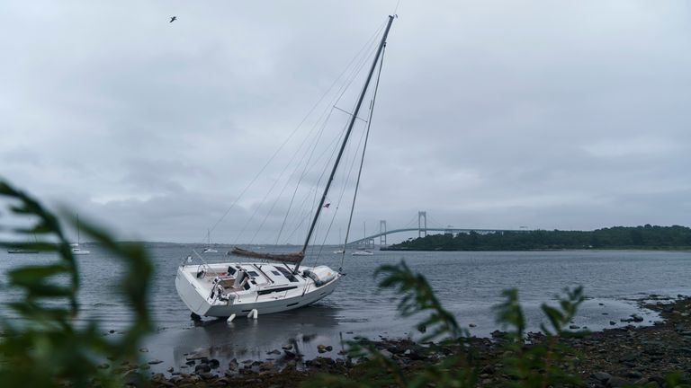 A sailboat sits washed up on shore after becoming loose from its mooring when Storm Henri passed through Jamestown. Pic: AP