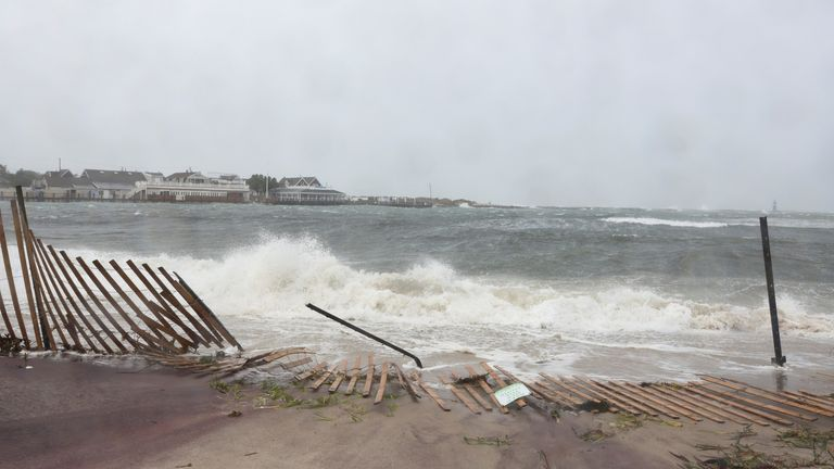 Waves crash onto a fallen fence during Tropical Storm Henri in Montauk, New York