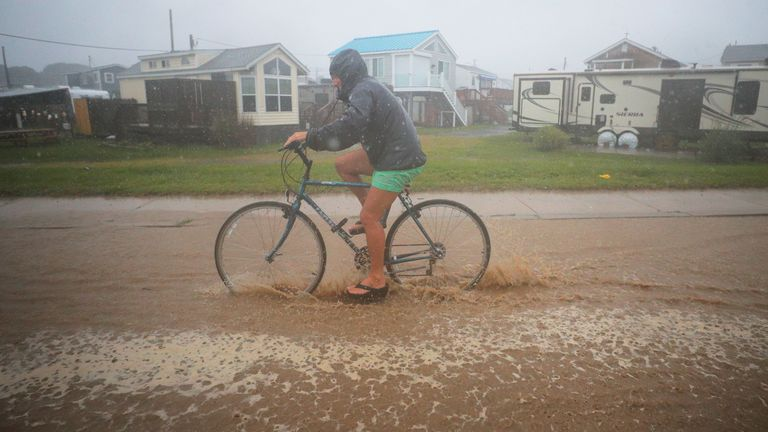 A bicyclist rides through a flooded street as Tropical Storm Henri approaches South Kingstown, Rhode Island