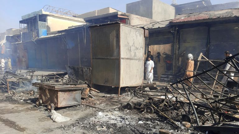 Afghans inspect damaged shops after fighting between Taliban and Afghan security forces in Kunduz city