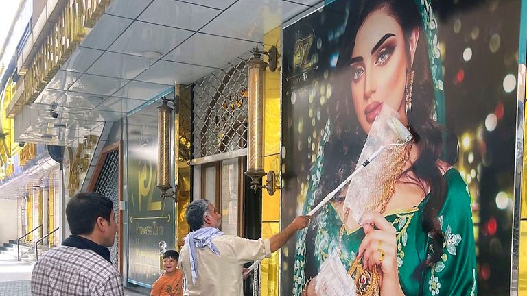 A worker at a beauty salon paints over a large photo of a woman on the wall in Kabul. Pic: Kyodo/AP