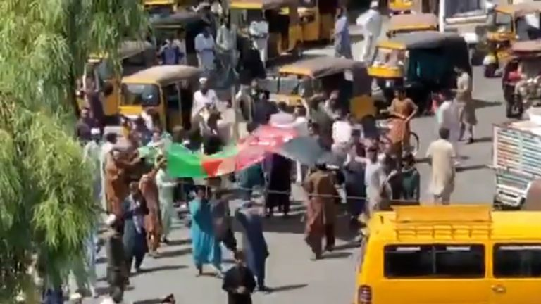 Protesters walk with the Afghan national flag in Jalalabad, where the Taliban's own flag was lowered a day before Afghanistan's independence day