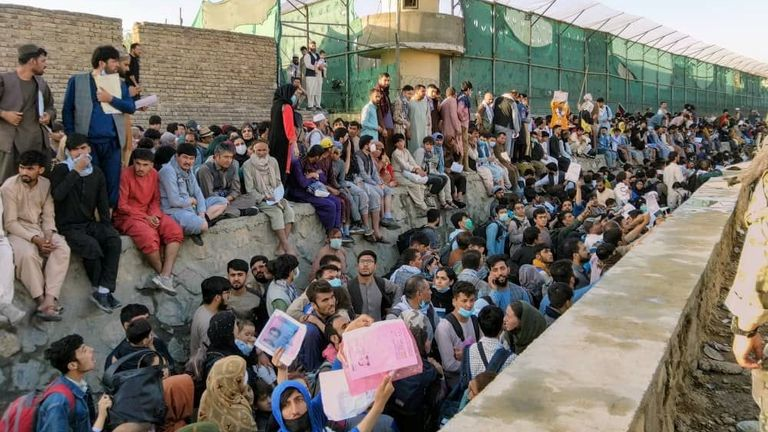 Crowds of people wait outside the airport in Kabul, Afghanistan, 25 August