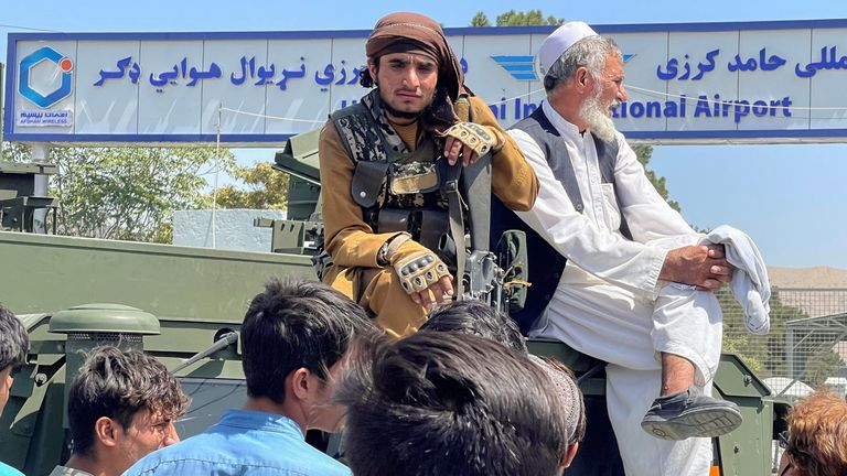 A member of Taliban forces (L) sits on a an armoured vehicle outside Hamid Karzai International Airport in Kabul, Afghanistan August 16, 2021. REUTERS/Stringer NO RESALES. NO ARCHIVES