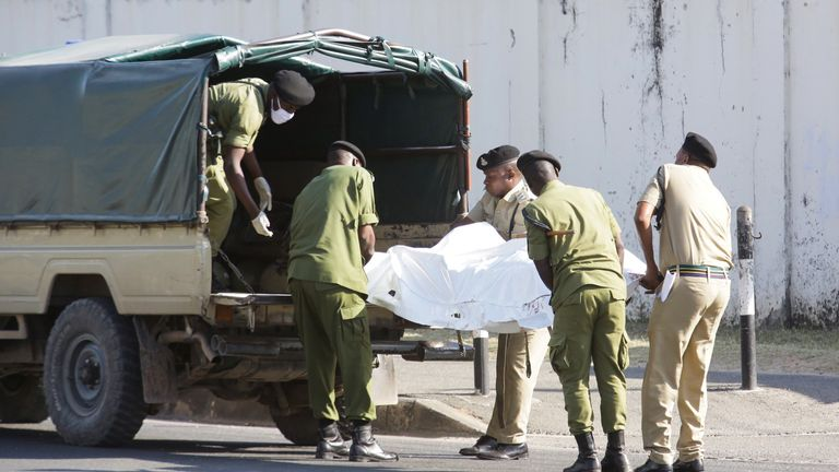 Police officers in bullet-proof vests who appear to be moving a dead body outside the embassy