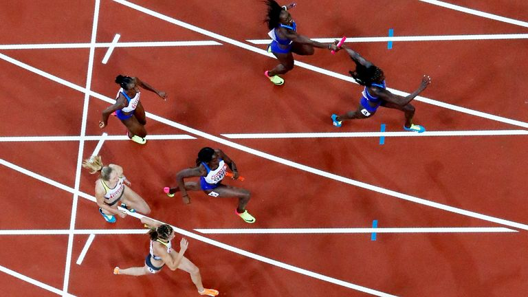 Athletics - World Athletics Championships - Women's 4x100 Metre Final - London Stadium, London, Britain – August 12, 2017. Morolake Akinosun of the U.S. passes the baton to Torie Bowie before winning the final as Daryll Neita of Great Britain receives the baton from Dina Asher-Smith. REUTERS/Fabrizio Bensch