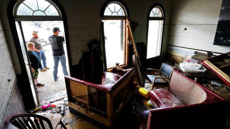 Kansas Klein, standing at right in the doorway, talks outside of his destroyed Bella Blak Pizzeria restaurant