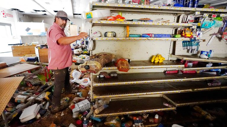 John Curtis, co-owner of Waverly Cash Saver grocery store, walks through his damaged store