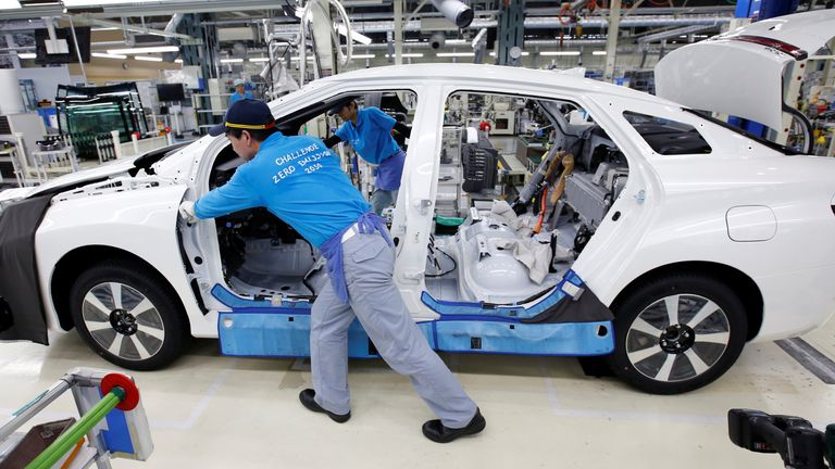 mployee of Toyota Motor Corp. pushes a body unit of a Mirai fuel cell vehicle (FCV) on it's assembly line at the company's Motomachi plant in Toyota, Aichi prefecture, Japan May 17, 2018