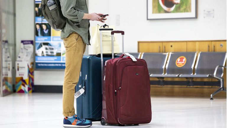 A passenger standing with luggage at George Best Belfast City Airport