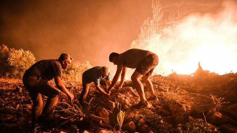 Local villagers try to get a fire under control in Kirli village near the town of Manavgat, in Antalya province, Turkey. Pic: AP