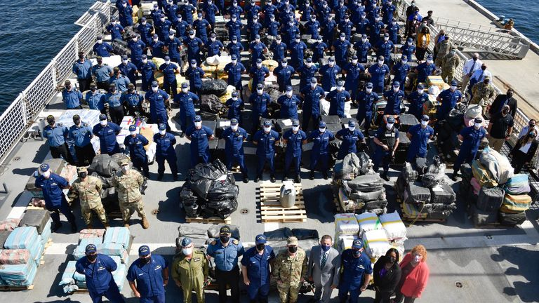 The ship's crew stand by the piles of seized drugs