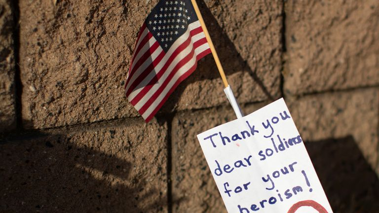 A note and U.S flag are shown placed at the main gate to U.S. Marine Base Camp Pendleton in Oceanside, California