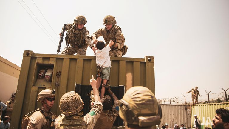 US troops hoist a child onto a container as evacuation efforts continue from Afghanistan